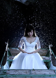 woman wearing white floral wedding dress sitting on bench