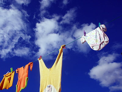 four assorted-color clothes hanging on rope