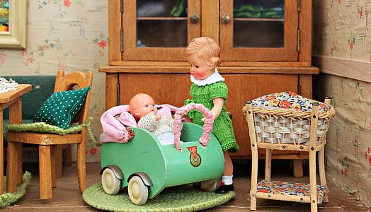 girl standing beside baby on stroller figurines