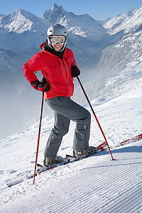 person in red jacket doing snow ski while holding ski poles during daytime