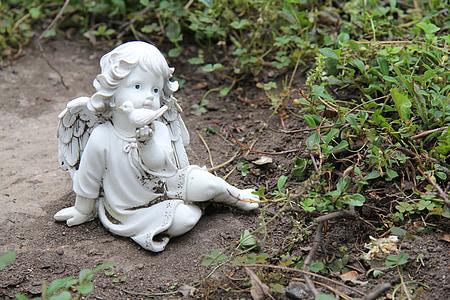 angel sculpture on gray concrete ground