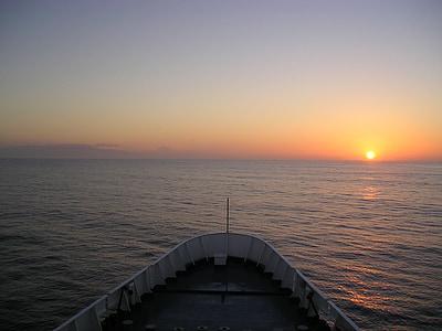 edge of white boat overseeing orange sunset