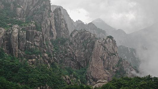 smoke on rock mountain with trees