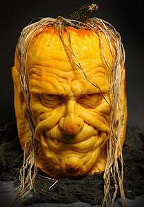man's face carved pumpkin on black floor