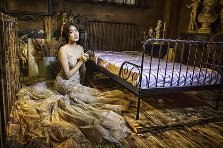 woman sitting beside metal bed