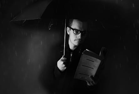 grayscale photograph of man reading book under umbrella during rain