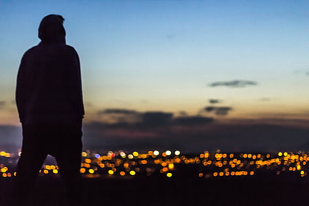 silhouette of man watching lights