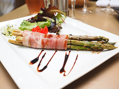 asparagus wrapped with bacon on white plate