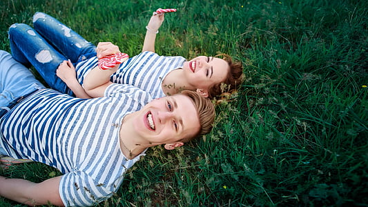 couple wearing gray-and-white striped shirts lying on green grass at daytime