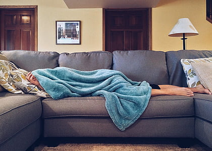 person sleeping in gray sofa