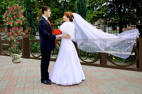 man and woman in wedding dress holding hands