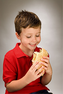 boy holding a sandwich