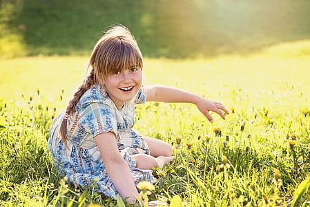 girl wearing blue dress sitting on green grass field