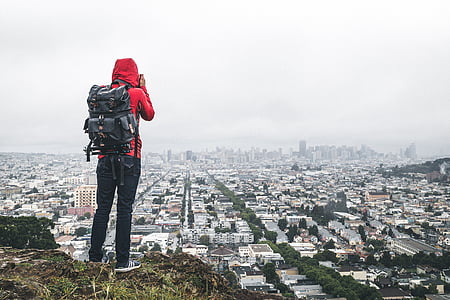 man standing on clip overlooking the city while taking photography