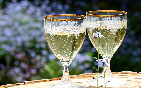 photo of two clear footed glasses filled with liquid