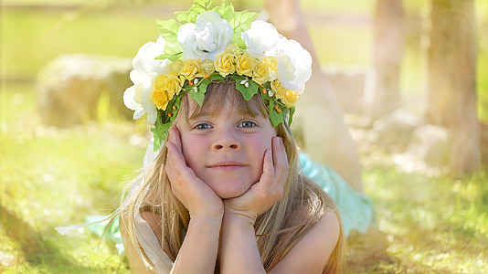 girl wearing flower crown lying on the grass