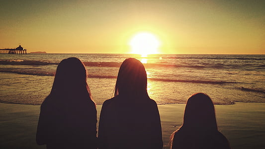 silhouette of three persons standing on seashore