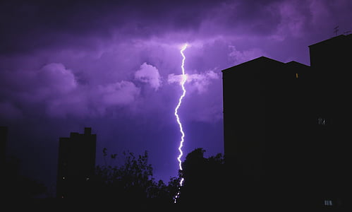 silhouette of buildings and lightning