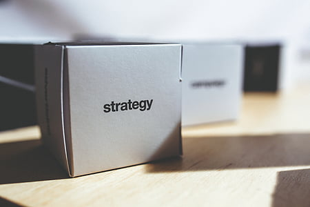 white Strategy box on brown wooden surface