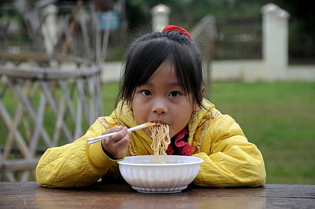 girl in yellow hoodie eatting noodles on table