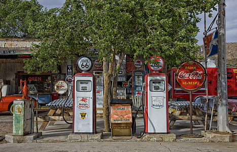 two white-and-red gasoline fuel pump station near tree at daytime