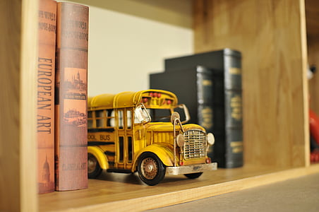 yellow school bus die-cast metal scale model on bookshelf