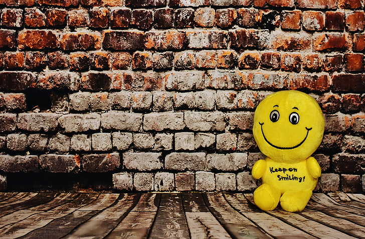 yellow plush toy leaning against wall