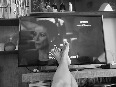 grayscale photo of person's feet in front of flat screen TV