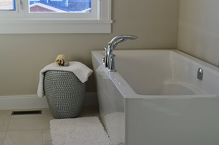 white fleece towel beside white bathtub