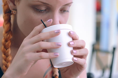 woman drinking on white disposable cup