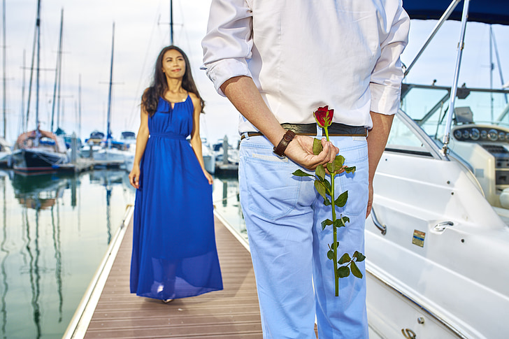 woman in blue sleeveless dress and man in white dress shirt and blue jeans holding red rose behind his back on pier bridge during daytime