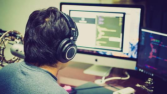 man wearing black headphones in front of computer