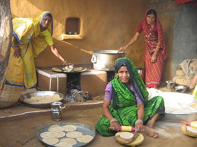 three women baking pancake near house