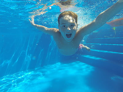 underwater photography of boy wearing red shorts