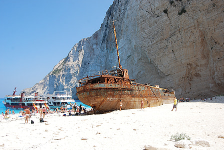 brown ship near gray rock formation