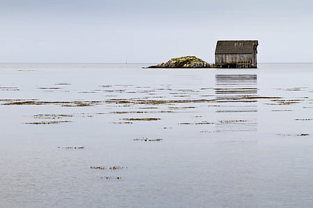 brown house beside rock formation beside body of water
