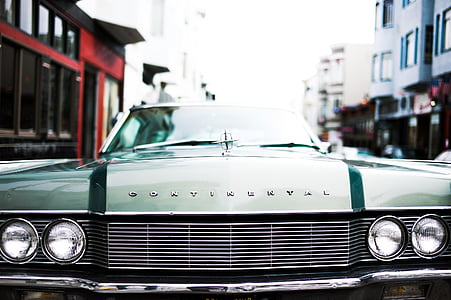 green Lincoln Continental on road near buildings during daytime