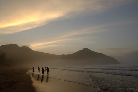 group of people walking on seashore near mountain range under golden hour