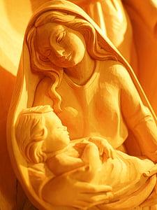 photo of woman holding child figurine