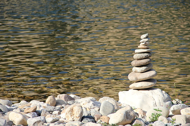 Royalty-Free photo: Stack of smooth river rocks near body of