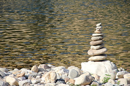 stack of smooth river rocks near body of water