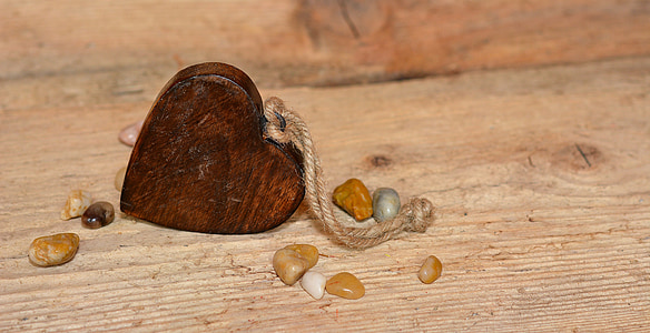 heart-shaped brown wooden keychain on brown surface