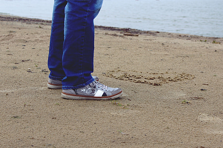 person in jeans and grey sneakers standing on beach sand