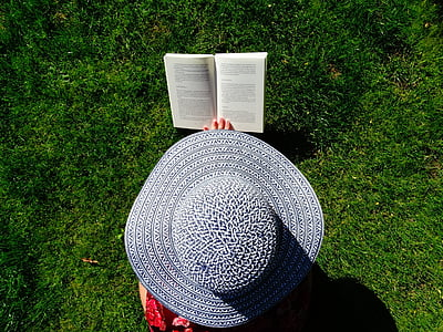 photograph of person wearing sun hat reading book on field of grass