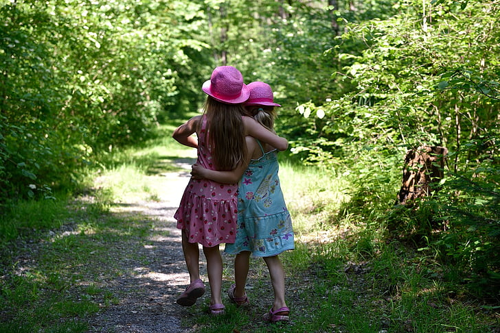 two girl's standing on green grass during daytime