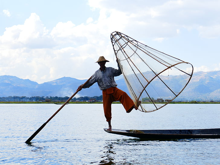 man standing in front of boat holding fishing basket