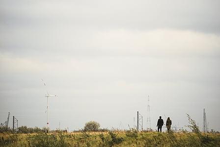 two people walking near green grass during daytime