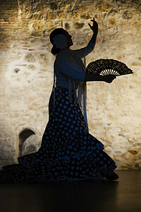 woman wearing white long-sleeved top and blue-and-white polka-dot long skirt holding fan