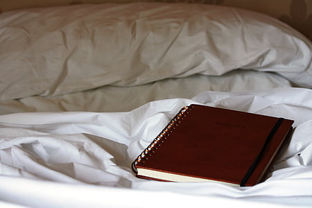 red spring book on top of bed inside the room