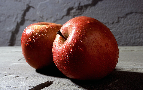 two red apples on gray stone
